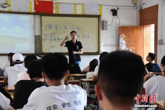 """6月9日,广西南宁市横县第二高级中学的教师阮杰正在给学生上最后一堂班会课,叮嘱注意事项,送别自己的第一届高三毕业生。1993年出生的阮杰在2016年毕业后选择回家乡任教。他工作第一年就当上了高一的班主任,一直到今年完成一个完整的三年任期,送走了第一批""""00后""""考生。三年间他从严肃的老师,变成了与学生打成一片的知心哥哥,有学生还专门给他画了一份漫画记录下他任教期间在学生心中角色的变化。王以照 摄"""