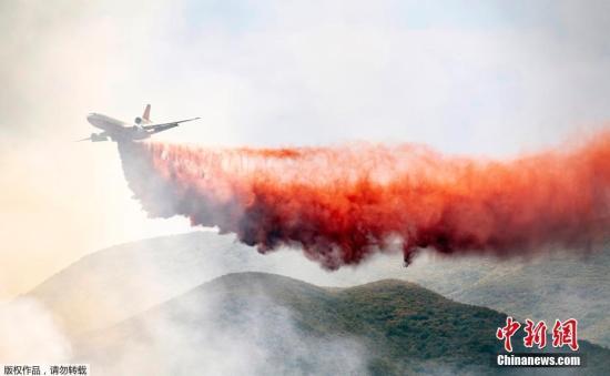 资料图:美国加州出动飞机进行灭火降温作业。