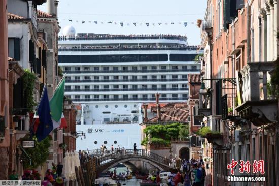 """资料图:游轮驶过威尼斯泻湖,巨大船身成为水城""""移动城墙""""。"""