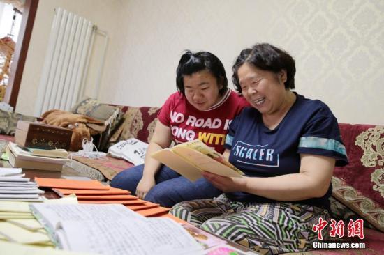 6月11日,张斐然与母亲刘蕊琴回顾自己所写的日记。张斐然今年20岁,先天失聪、语言功能严重障碍,12年来,张斐然在母亲的帮助鼓励下,写下了90本日记。在2019年单招高考中,张斐然同时被长春大学、西安美术学院、天津理工大学等七所高校录取,最终张斐然选择了重庆师范大学特殊教育专业,希望将来能够帮助和自己一样的人。中新社记者 张远 摄
