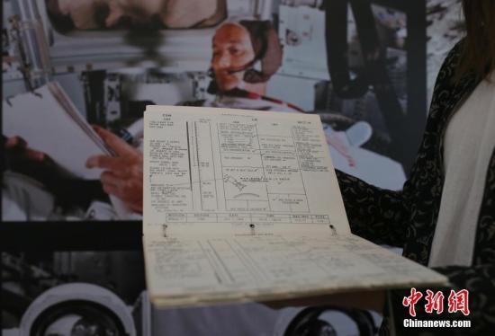 """6月13日,佳士得拍卖工作人员在北京展示""""阿波罗11号登月舱航行记录册""""。这本标注为——""""阿波罗11号登月舱航行记录册,(休斯顿):载人航天中心,飞行计划部,1969年6月19日至7月12日"""",并夹杂着月表尘埃的册子,曾跟随""""鹰号""""登月舱登陆月球,并由尼尔?阿姆斯特朗及巴兹?奥尔德林在登月后撰写注释。估价为7,000,000至9,000,000美元。该藏品将于7月18日在佳士得纽约""""人类史上的一大步:纪念阿波罗11号太空探索50周年""""专场中进行拍卖。中新社记者 杨可佳 摄"""