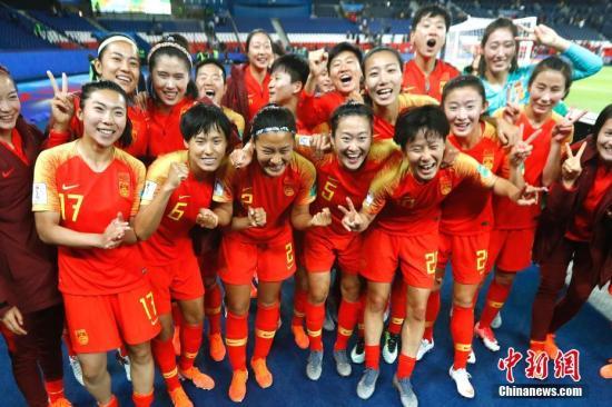 原料图:中国女足制服南非取得本届世界杯首胜后,在。球场边高昂留念。 中新社记者 富田 摄