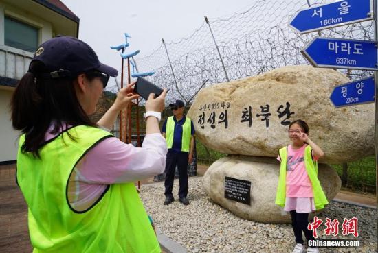 """2019年,韩国首次向公众开放非军事区徒步游。图为民众在""""金刚通门""""旁边留影,这曾是韩国游客前往朝鲜金刚山旅游的必经之路。中新社记者 曾鼐 摄"""