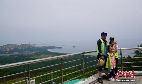 资料图:韩国民众在金刚山展望台合影,身后为朝鲜境内的金刚山。<a target='_blank' href='http://www.chinanews.com/'>中新社</a>记者 曾鼐 摄