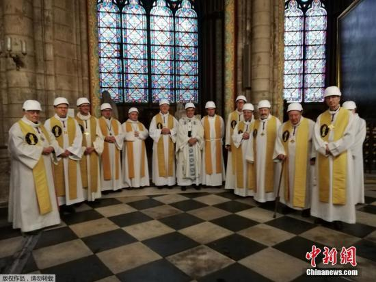 资料图:当地时间6月15日,巴黎圣母院发生火灾的两个月后,在教堂内举行首次弥撒祈福活动。据悉,出于安全考虑,参与此次活动的民众和神职人员都带上了安全帽。