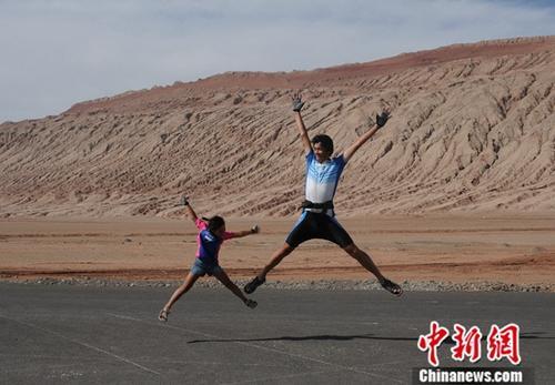 2009年9月,到达古丝绸之路骑行的终点火焰山,父女俩跳跃欢呼。<a target='_blank' href='http://www-chinanews-com.xiangxinshi.com/'>中新社</a>发 陈守忠 供图