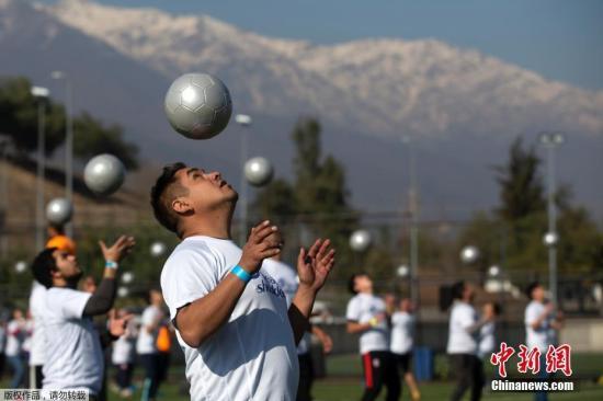资料图:智利圣地亚哥,数百人同时顶球5秒,试图创造一项新的吉尼斯世界纪录。