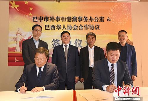 巴中市外事台侨和港澳事务办公室主任(前排左)与巴西华人。协会会长张伟签约。中新社记者 莫成。雄 摄