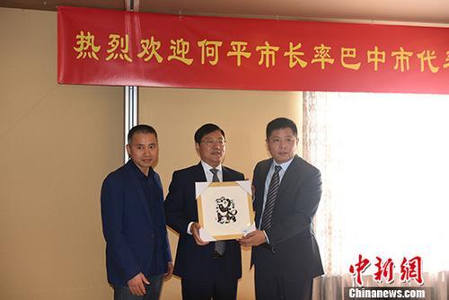 巴中市委副书记、市长何平(中)向巴西华人。协会会长张伟(右)施舍祝贺品。中新社记者 莫成。雄 摄
