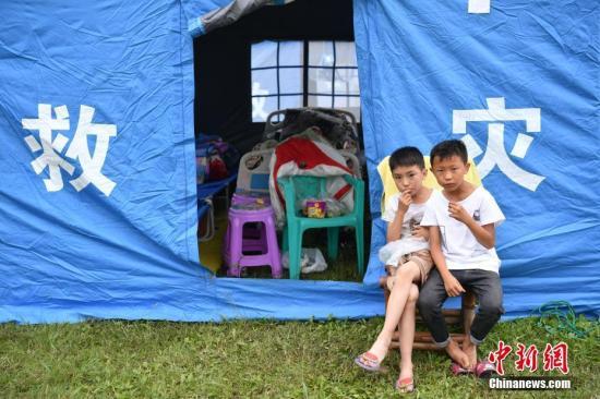 6月18日,四川宜賓長寧6.0級地震發生后第二天,在震中雙河中學操場里,用于臨時安置災區民眾的救災帳篷陸續搭建起來。在臨時集中安置區里,一些來自地震災區的孩子們在各個角落玩耍、互相嬉戲。張浪 攝