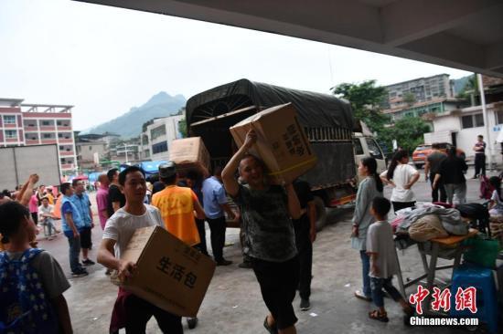 灾区民众与工作人员携手搬运救灾物资。张浪 摄