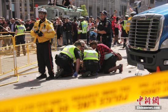当地时间6月17日下午,在加拿大多伦多市举行的多伦多猛龙队夺得美国职业篮球联赛(NBA)冠军庆功集会现场发生枪击案。图为警员等展开紧急救治。<a target='_blank' href='http://www.chinanews.com/'>中新社</a>记者 余瑞冬 摄