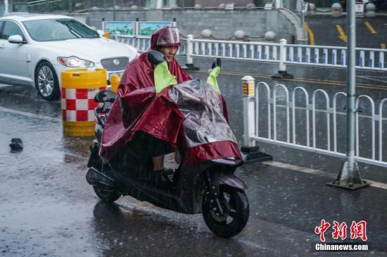 6月18日,市民冒雨骑行。当日午后,一场大雨袭击广西南宁,市民出行受阻。 中新社记者 陈冠言 摄