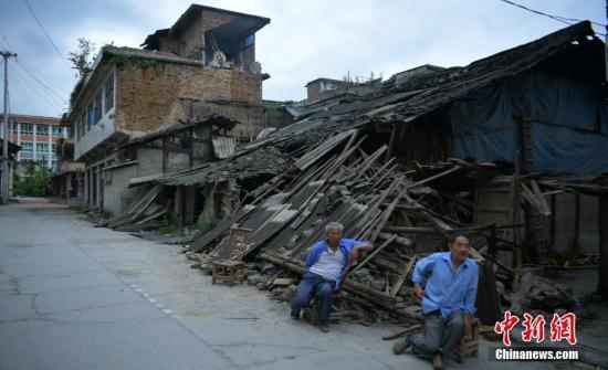 6月18日,四川长宁双河镇,两位老人坐在因地震倒塌的民房前。四川省宜宾市长宁县6月17日22时55分发生6.0级地震,震中位于长宁县双河镇,许多房屋在地震中受损严重。中新社记者 刘忠俊 摄