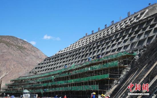 苏洼龙水电站项目是西藏第一个装机容量超百万千瓦的大型水电工程,装机容量120万千瓦。计划7月完成引水发电系统开挖,年底完成1至4号机组锥管安装、溢洪道开挖和大坝防渗结构施工,2021年投产。图为建设中的苏洼龙水电站项目大坝。 中新社发 钟欣 摄
