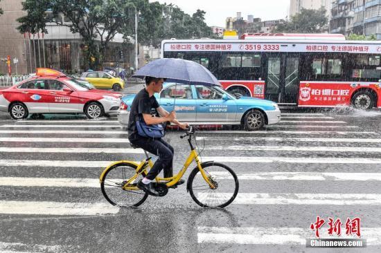 6月24日,广州,民众冒雨出行。当日14时42分,广州气象灾害应急指挥部办公室发布广州市气象灾害(暴雨)Ⅰ级应急响应。截止当日16时,广州中北部出现大到暴雨,南部出现中到大雨,多地发布暴雨红色预警。 /p中新社记者 陈骥旻 摄