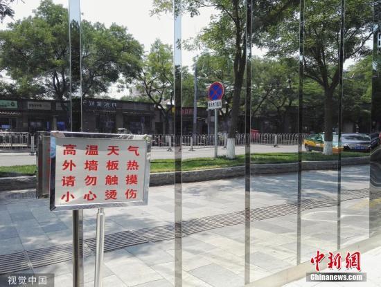 """6月24日,据北京市气象局官方微博消息,北京市气象台6月24日9时继续发布高温蓝色预警信号。位于北京东直门内一座建筑在阳光下闪闪发光,烈日炎炎,阳光照射使得镜面外墙的温度升高,门前摆放了""""小心烫伤""""的提示牌提示来往路人。图片来源:视觉中国"""
