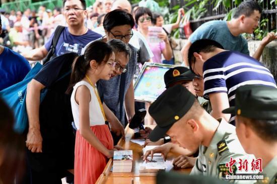6月23日早上,香港市民提早排队领取解放军驻港部队军营参观券。<a target='_blank' href='http://www.interproperty4u.com/'>中新社</a>记者 李志华 摄