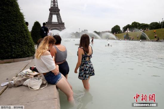 """据外媒近日报道称,欧洲多国本周将迎来罕见热浪:法国巴黎27日的气温将高达40℃,德国部分地区的气温预计突破41℃。此外,西班牙、比利时、意大利、瑞士等欧洲国家都将于本周进入高温""""炙烤""""模式。图为当地时间6月24日,民众在法国巴黎菲尔铁塔对面的喷泉内乘凉。"""