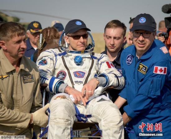 """當地時間6月25日,搭載三名宇航員的""""聯盟MS-11""""號飛船從國際空間站成功返回地球,并在哈薩克斯坦境內著陸。三名宇航員分別是俄羅斯宇航員科諾年科、加拿大宇航員圣雅克和美國女宇航員麥克萊恩。圖為工作人員協助加拿大宇航員圣雅克出艙。"""