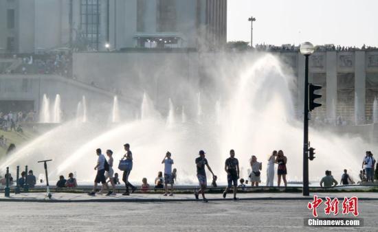 """资料图:当地时间6月27日,巴黎埃菲尔铁塔对面的""""华沙喷泉""""完全对外开放。法国遭遇史上罕见热浪袭击,最高气温超越历史同期。法国首都巴黎的气温居高不下,最近两天的最高气温一直在34摄氏度以上。中新社记者 李洋 摄"""