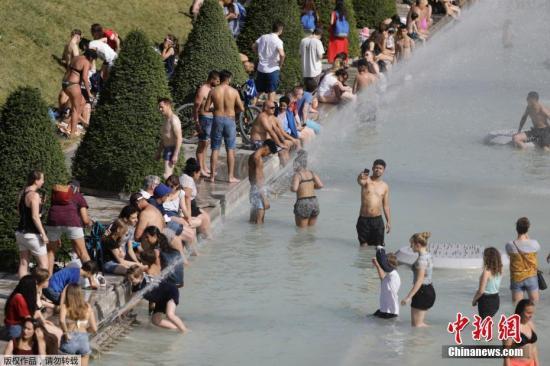 资料图:当地时间2019年6月28日,法国巴黎,法国遭遇连日极端高温天气袭击,众多巴黎市民和游客聚集在埃菲尔铁塔前的喷水池泡水降温。