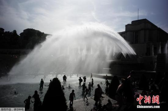 当地时间2019年6月28日,法国巴黎,法国遭遇连日极端高温天气袭击,众多巴黎市民和游客聚集在埃菲尔铁塔前的喷水池泡水降温。