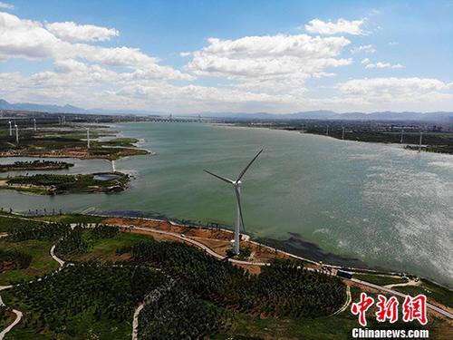 """6月29日,航拍北京官厅风电场。北京官厅风电场位于河北省怀来县官厅水库南岸,距北四环70公里,是传统意义上的北京""""上风口""""。北京官厅风电场工程是北京市首次风能资源的规模化利用。 <a target='_blank' href='http://www.chinanews.com/'>中新社</a>记者 杨艳敏 摄"""