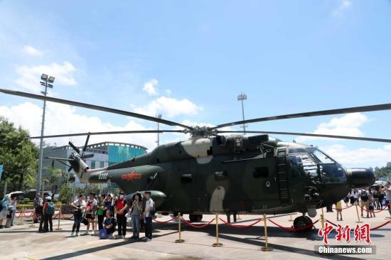 7月1日上午,香港中学生在直升机前留影。驻香港部队6月30日至7月1日连续两天开放昂船洲军营,其中7月1日为香港青年学生专场,两天活动共吸引约3万名市民和青年学生入营参观,近距离感受军队和军人独有的文化和魅力。当天,军营举行升旗仪式,军乐队列表演,格斗技术展示,刺杀操表演,猎人战斗表演,陆、海、空军武器装备展示,后勤保障装备与器材展示等。<a target='_blank' href='http://www.chinanews.com/'>中新社</a>记者 洪少葵 摄