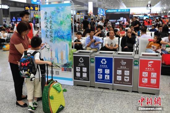资料图:志愿者在铁路上海虹桥站宣传垃圾分类。殷立勤 摄