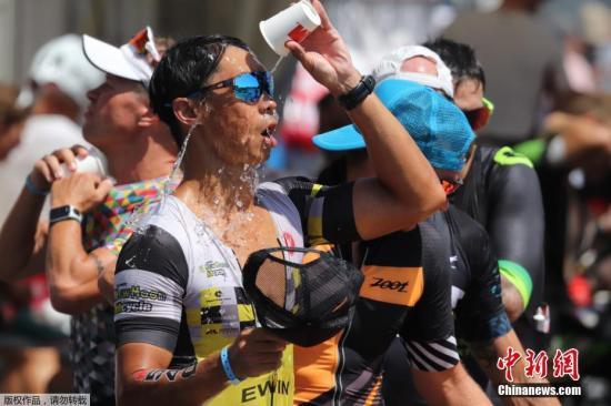 """一向比较凉爽的德国也没有躲过这股热浪,多地都经历了历史同期以来的最高温度。图为在法兰克福举行的铁人三项比赛中,运动员用饮用水""""冲凉""""。"""