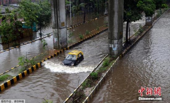 材料图@员天工夫2019年7月2日,印度孟购,孟ね逢连日暴雨侵袭,街讲被吞没,一辆轿车脱过一条浸火的街讲。