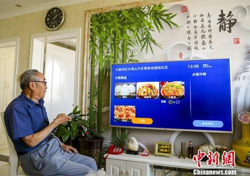 新疆乌鲁木齐市团结社区,老人通过电视订第二天的中餐。 中新社记者 刘新 摄