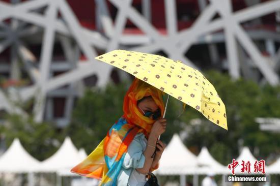 资料图片为:游客撑伞游览北京奥林匹克公园。中新社记者 富田 摄