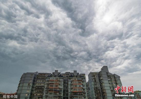2019年7月5日上午9时,北京发布了今年第一个全市性暴雨蓝色预警,北京市气象局已启动暴雨Ⅳ级应急响应。预计,今后三天,北京将雨势不断,同时,这也将是华北一带入汛以来最明显的一次降雨过程。图为北京东城区,强降雨天气来袭,天空宛如科幻大片。杨澄 摄 图片来源:视觉中国