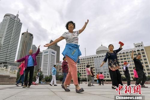 7月5日清晨,新疆乌鲁木齐,民众在人民广场上跳舞运动,锻炼身体。中新社记者 刘新 摄