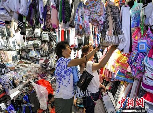7月5日,新疆乌鲁木齐市一综合市场内,琳琅满目的商品吸引民众前来选购。中新社记者 刘新 摄