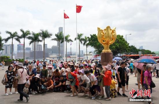 资料图:游客在香港金紫荆广场观光拍照。中新社记者 张炜 摄