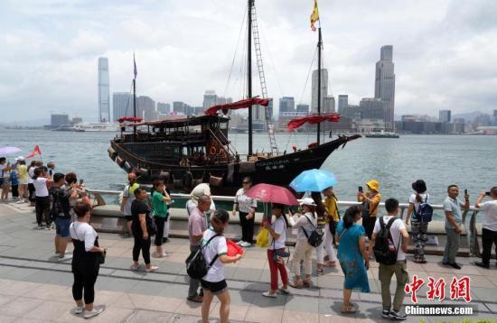 资料图:游客在香港金紫荆广场附近的海滨观光拍照。<a target='_blank' href='http://www.chinanews.com/'>中新社</a>记者 张炜 摄