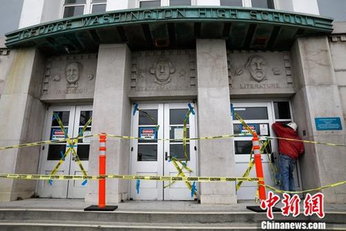 当地时间7月8日,美国旧金山的乔治・华盛顿高中门口,一位施工工人透过玻璃往学校内部张望。该校校董会近日投票决定,将花费60万美元涂盖校内一幅拥有83年历史的壁画。决定一经公布,便引发当地社会的争论。目前,校内主体建筑正进行封闭维修,有壁画的区域已拉起警戒线,但并未施工。中新社记者 刘关关 摄