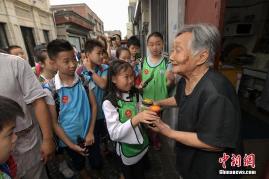 """7月10日,30余名北京小学生组成""""小记者团""""前往前门及附近老街巷,探访当地传统老字号故地,记录体验传统文化。中新社记者 崔楠 摄"""
