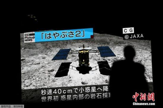 """资料图:当地时间2019年7月11日,日本神奈川县,""""隼鸟2号""""任务控制室,日本宇宙航空研究开发机构(JAXA)11日接到了显示探测器""""隼鸟2号""""已经在小行星""""龙宫""""上着陆的信号。据悉,这将是""""隼鸟2号""""继2月之后的第二次着陆,目的是采集4月制造人造陨石坑时从地下向周围喷出的物质。如果成功,其在""""龙宫""""上的主要任务将基本完成。图为日本探测器""""隼鸟2号""""着陆画面。"""