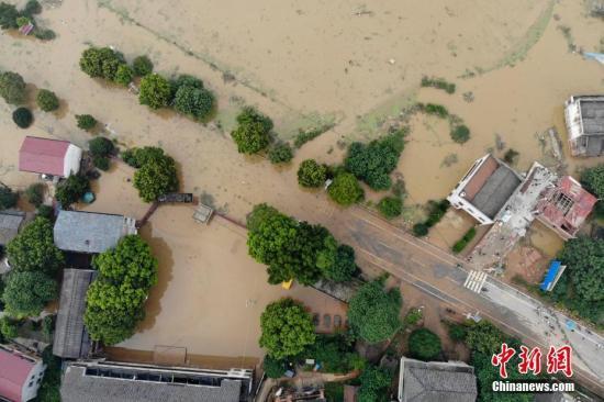 7月11日,湖南衡东县多个乡村与一些道路仍然浸泡在洪水中。连日来,衡东县出现了持续强降雨天气,造成该县17个乡镇、233个村、22个社区普遍受灾。衡东县防汛抗旱指挥部启动防汛Ⅰ级响应急响应。10日,衡东县霞流镇洣河村洣水河堤发生两处漫堤决口,决口宽度分别约为50米和30米,霞流镇第一时间组织附近村民转移。图为衡山县通往衡东县的东健大道被洪水阻断。杨华峰 摄
