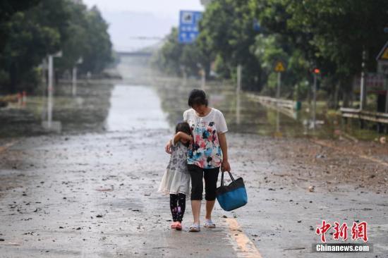 7月11日,湖南衡东县多个乡村与一些道路仍然浸泡在洪水中。连日来,衡东县出现了持续强降雨天气,造成该县17个乡镇、233个村、22个社区普遍受灾。衡东县防汛抗旱指挥部启动防汛Ⅰ级响应急响应。10日,衡东县霞流镇洣河村洣水河堤发生两处漫堤决口,决口宽度分别约为50米和30米,霞流镇第一时间组织附近村民转移。图为两位村民在东健大道上折返回家。杨华峰 摄