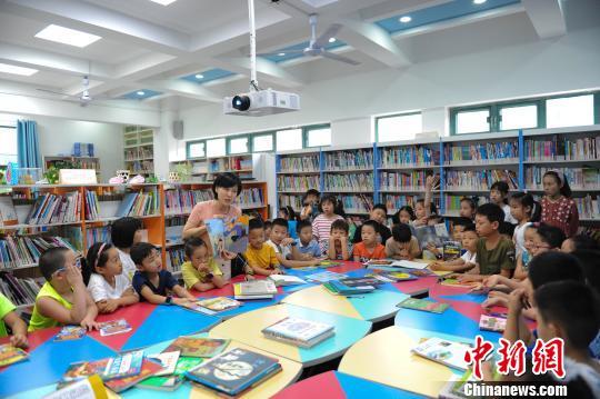 资料图:学校图书馆里,志愿者带领孩子们一起学习、读书。张娅子 摄