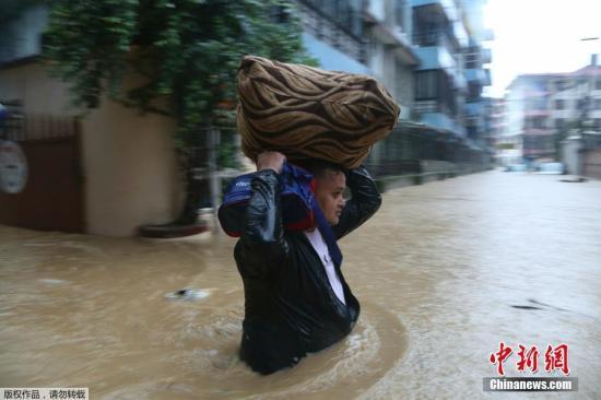 当地时间7月12日,泊尔加德满都,当地迎来雨季,城区街道被雨水淹没,居民出行㚾,当地派出军人确保居民安全。