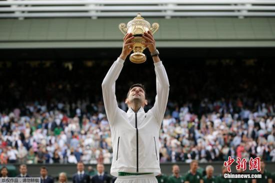 """当地时间2019年7月14日,温布尔登网球公开赛男单决赛中,赛会1号种子德约科维奇与""""草地之王""""费德勒上演史诗对决。德约科维奇最终以7-6(5)、1-6、7-6(4)、4-6、13-12(3)险胜瑞士天王,豪夺生涯第5座温网奖杯,这也是他第16个大满贯冠军。图为德约科维奇庆祝温网夺冠。"""