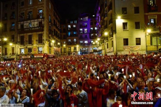 本地工夫7月15日,西班牙潘普洛,狂悲者下举白领巾战烛炬唱歌庆贺奔牛节的完毕。