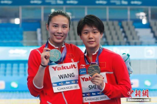 7月15日,中国选手施廷懋(右)/王涵手持奖牌合影。当日,在韩国光州举行的2019光州游泳世锦赛女子双人3米跳板决赛中,中国组合施廷懋/王涵以342.00分的成绩获得冠军。中新社记者 韩海丹 摄