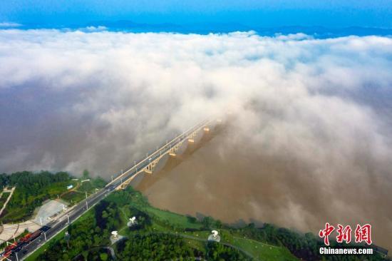 7月17日,无人机空中航拍江西省吉安市新干县城市云雾美景。当初升的太阳早晨从东方的天空缓缓露出脸来,城市上空的雨水转化为弥漫空中的云海、水雾,在湖泊、湿地、河流的上空缓慢移动开来,美若仙境。李福孙 摄